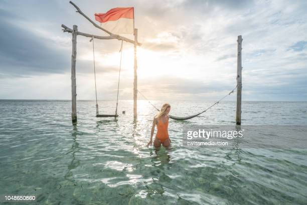 young woman walking into water near swing over the sea, beautiful and idyllic landscape. people travel vacations concept - gili trawangan stock photos and pictures