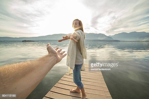 Young woman walking on a jetty holding a man's hand.