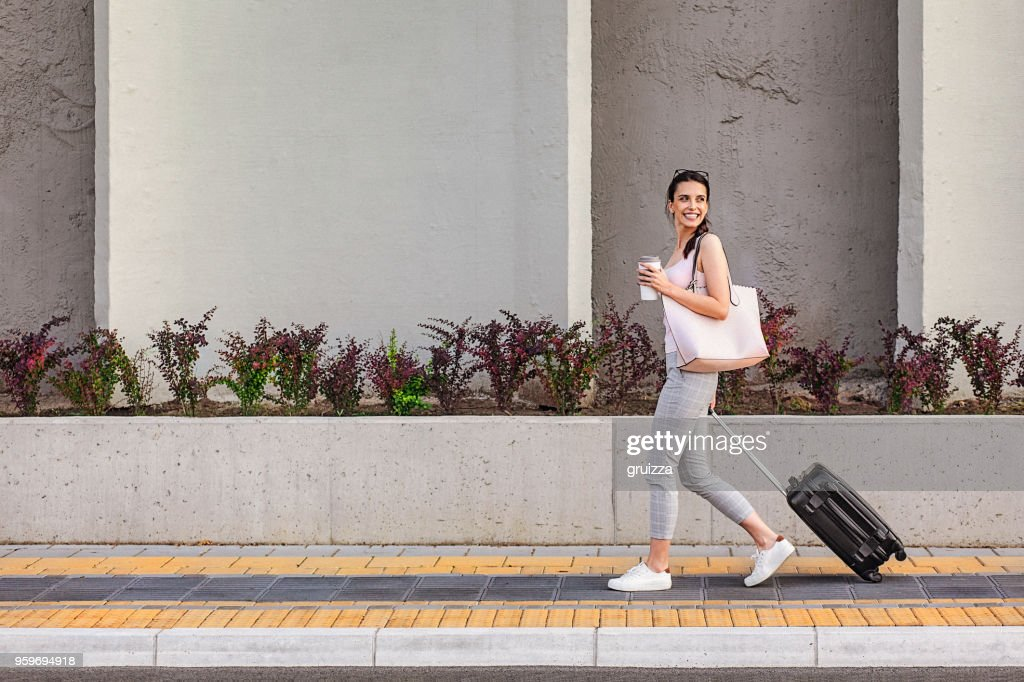 Young woman walking on a sidewalk beside the concrete wall and pulling a small wheeled luggage : Stock Photo