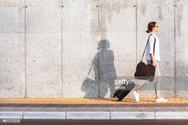 young woman walking on a sidewalk beside the concrete wall and pulling a small wheeled luggage - passenger stock pictures, royalty-free photos & images