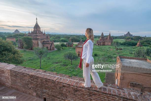 Young woman walking on ancient temple in Myanmar