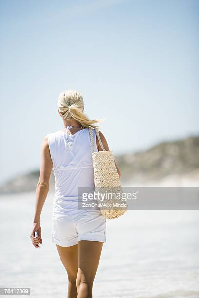 young woman walking on beach, carrying beach bag, rear view - woman carrying tote bag stock photos and pictures