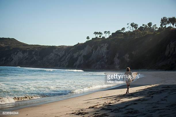 young woman walking on beach, malibu, california, usa - malibu foto e immagini stock