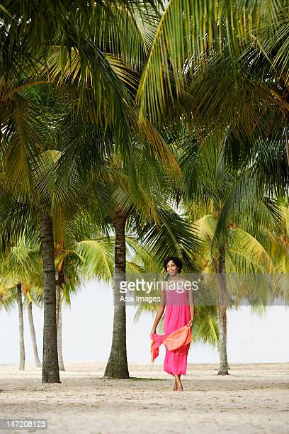 Young woman walking on beach, under coconut trees.