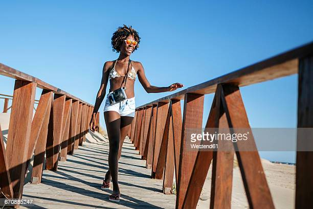 young woman walking on boardwalk on the beach - bikini top stock pictures, royalty-free photos & images