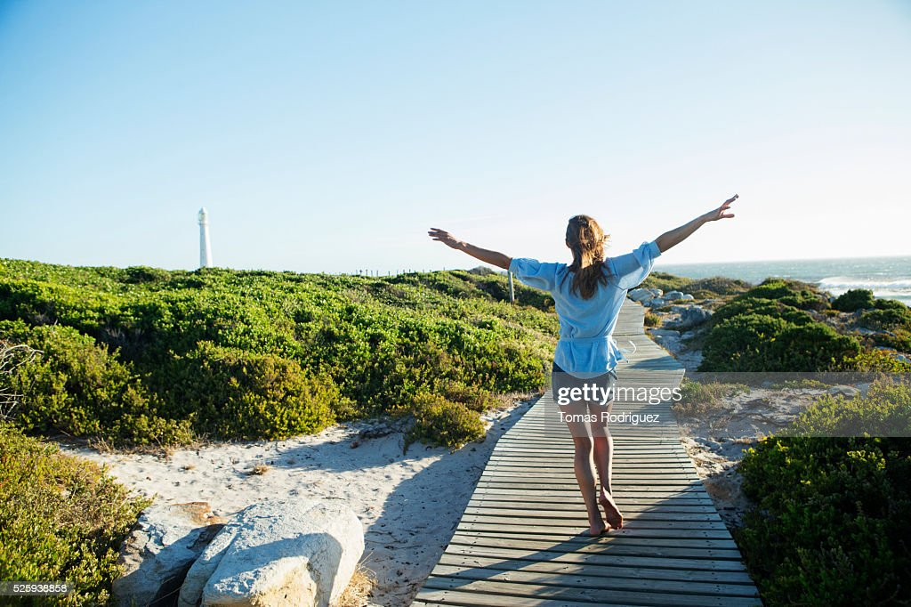 Young woman walking on boardwalk : Bildbanksbilder