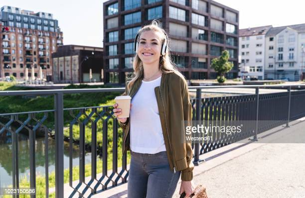 young woman walking on bridge, drinking coffee, listening music with headphones - three quarter length stock pictures, royalty-free photos & images