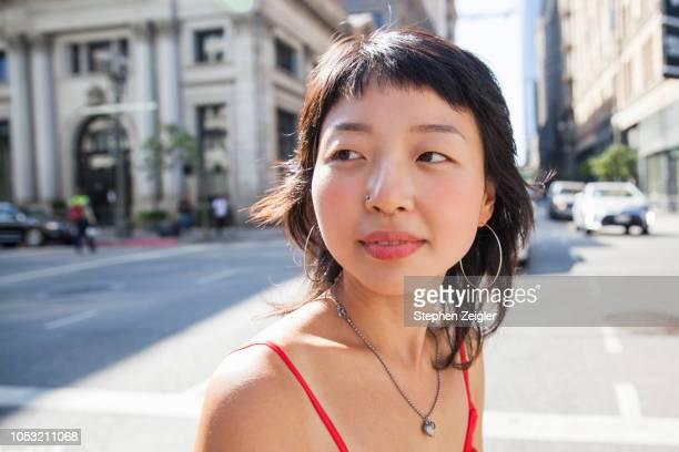 young woman walking on city street - cadera mujer fotografías e imágenes de stock