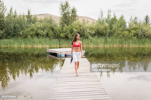 young woman walking on dock at forest lake - bikini top stock pictures, royalty-free photos & images
