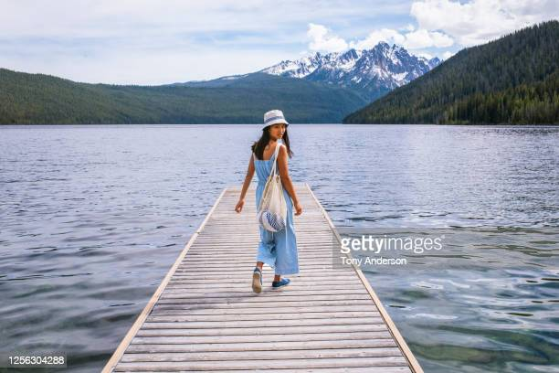 young woman walking on dock at mountain lake - looking over shoulder stock pictures, royalty-free photos & images