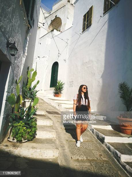 young woman walking on footpath amidst buildings in city - ostuni stock photos and pictures