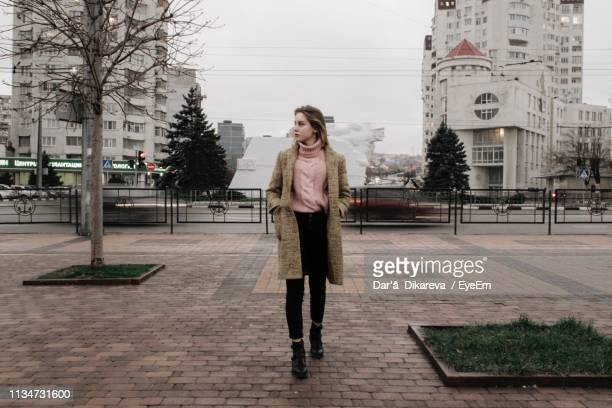 young woman walking on footpath in city - coat ストックフォトと画像