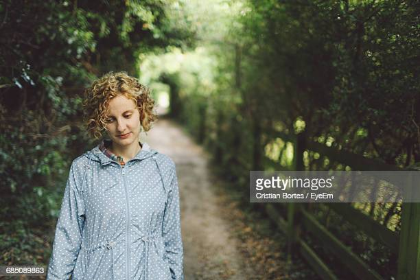 young woman walking on footpath - bortes stockfoto's en -beelden
