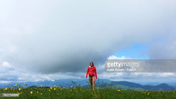 Young Woman Walking On Grassy Field Against Cloudy Sky