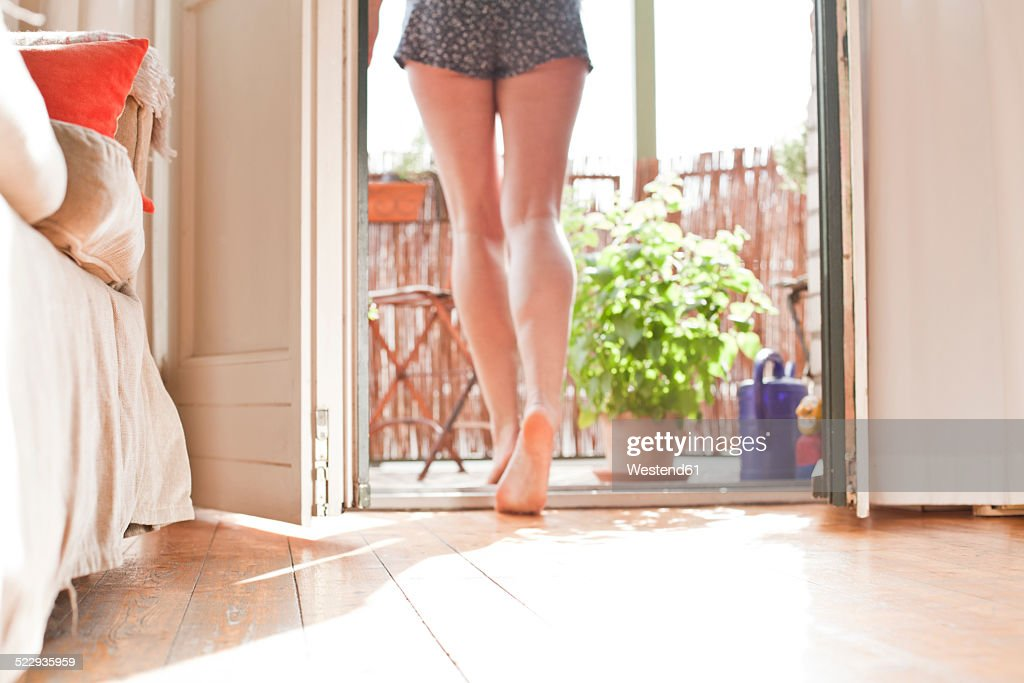 Young woman walking on her balcony : Stock Photo
