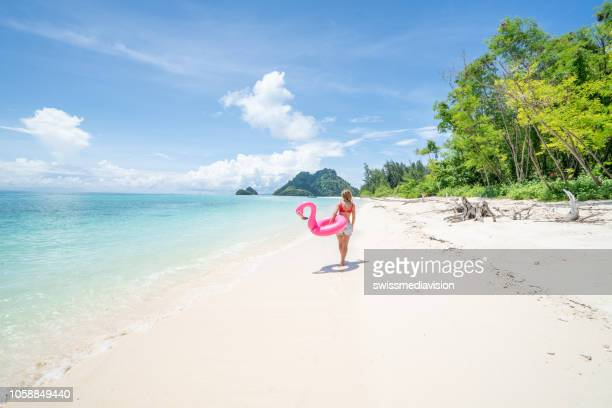 young woman walking on idyllic beach with inflatable flamingo in the islands of thailand. people travel destinations fun and cool attitude concept - thailand stock pictures, royalty-free photos & images