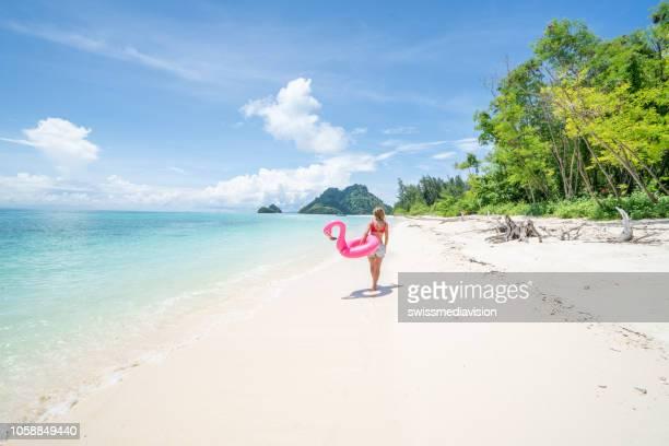 ung kvinna gå på idyllisk strand med uppblåsbar flamingo i thailand öarna. människor reser resmål roliga och coola attityd koncept - thailand bildbanksfoton och bilder