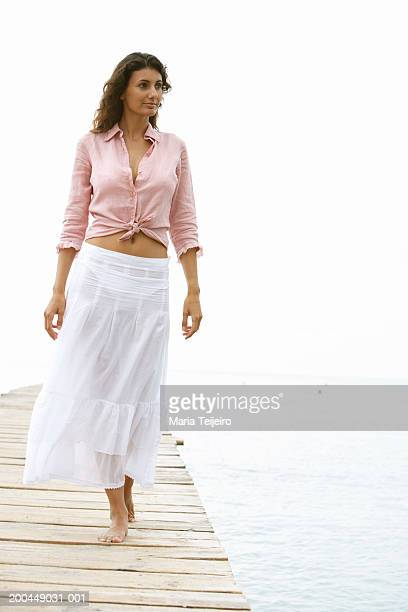 young woman walking on jetty, looking to one side - women in see through shirts stock photos and pictures