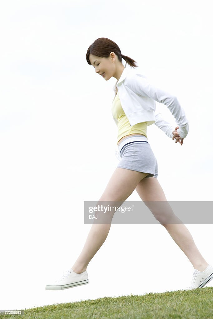 Young Woman walking on lawn, low angle view : Photo