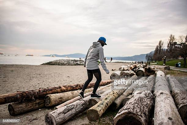 young woman walking on logs, rear view, english bay, vancouver, canada - english bay stock photos and pictures