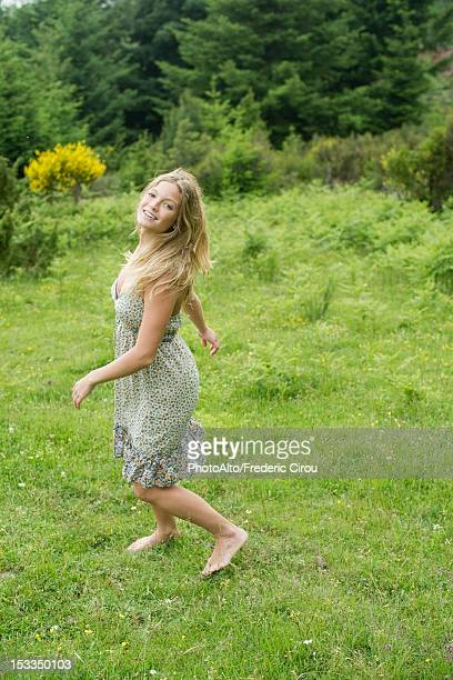 Young woman walking on meadow with barefeet