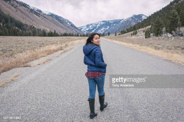 young woman walking on mountain road on cold cloudy day - looking over shoulder - fotografias e filmes do acervo