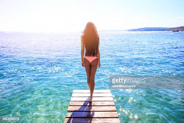 young woman walking on pier - women in harmony stock pictures, royalty-free photos & images