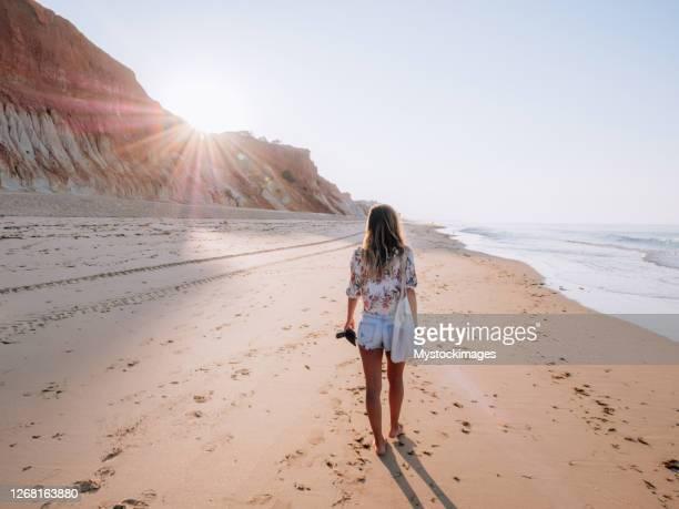 jeune femme marchant sur la plage portugaise au lever du soleil - océan atlantique photos et images de collection