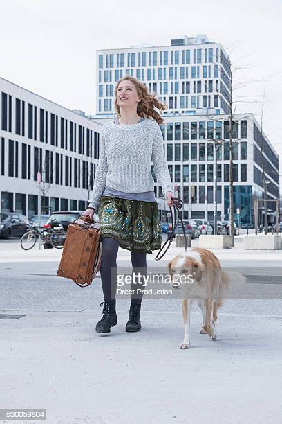 Young woman walking on road with dog and suitcase, Munich, Bavaria, Germany