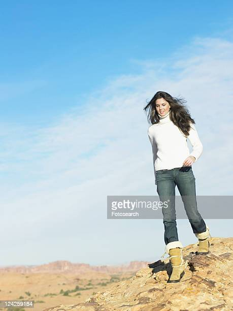 Young woman walking on rock