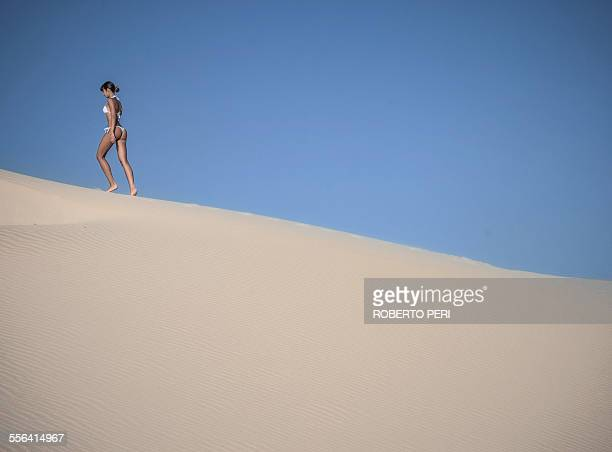 Young woman walking on sand dune against clear blue sky