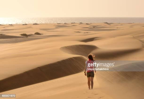 Young woman walking on sand dunes, Maspalomas, Canary islands