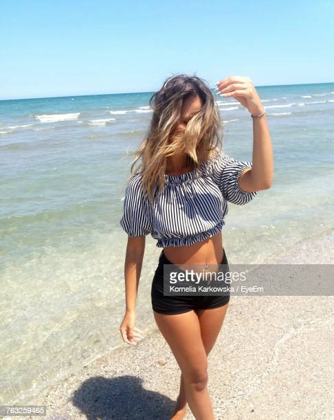 young woman walking on shore at beach - women in daisy dukes stock photos and pictures