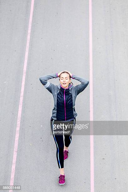 Young woman walking on sport track