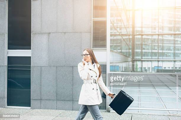 Young woman walking on street and talking on phone