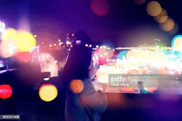 Young woman walking on street at night, Paris