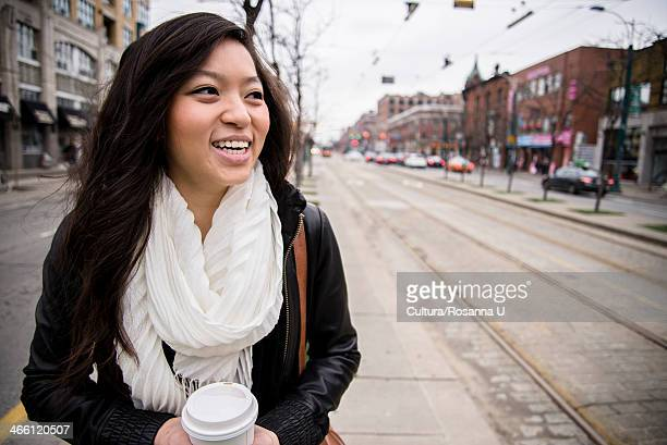 Young woman walking on street in city, smiling