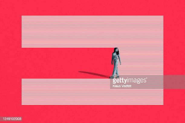 young woman walking on striped studio backdrop - looking over shoulder stock pictures, royalty-free photos & images