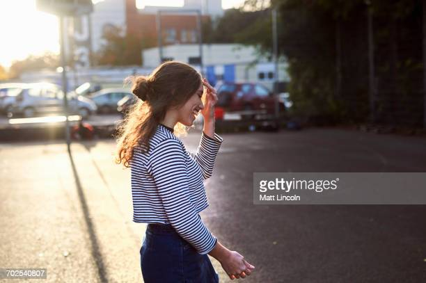 Young woman walking on sunlit street
