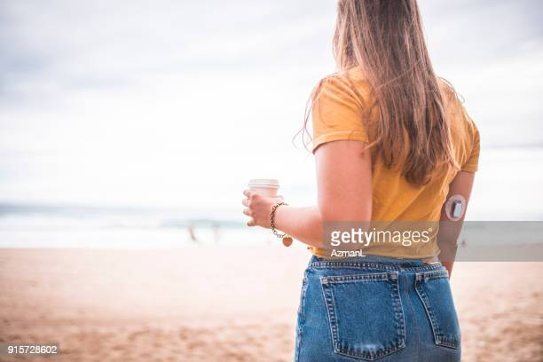 Young woman walking on the beach and holding coffee cup