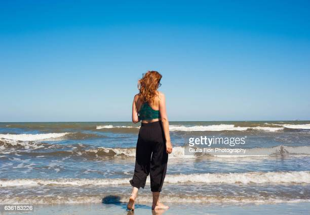 young woman walking on the beach - culottes stock pictures, royalty-free photos & images