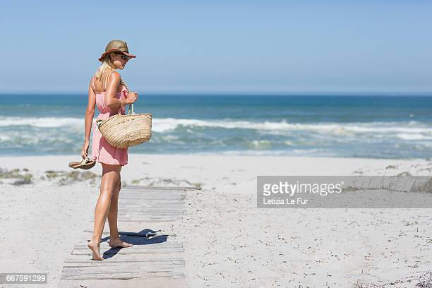 young woman walking on the beach - woman carrying tote bag stock photos and pictures