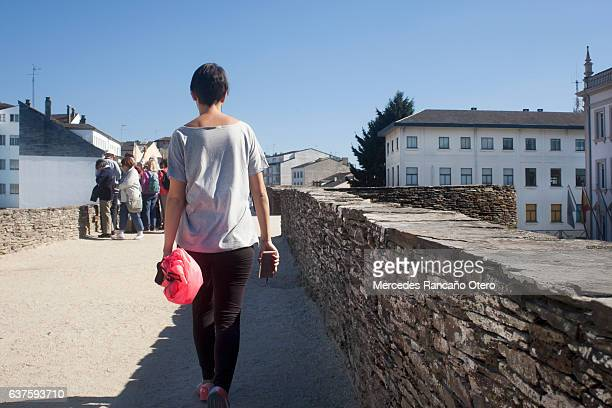 """young woman walking on the """"muralla"""", lugo, spain. - muralla stock photos and pictures"""