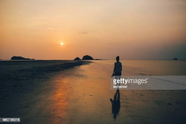 mulher jovem caminhando na praia arenosa de koh lanta, tailândia - low key - fotografias e filmes do acervo