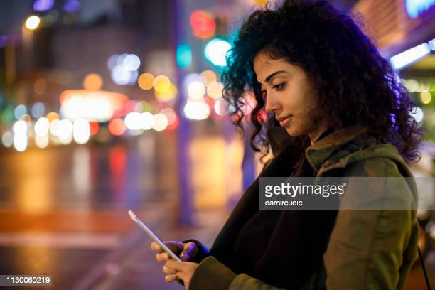 young woman walking on the street at night - catching stock pictures, royalty-free photos & images