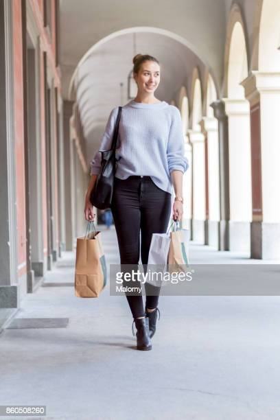 Young woman walking on the street with shopping bags in both hands.