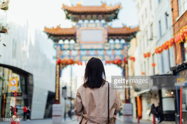 young woman walking on the streets at chinatown, london - east asian ethnicity stock pictures, royalty-free photos & images