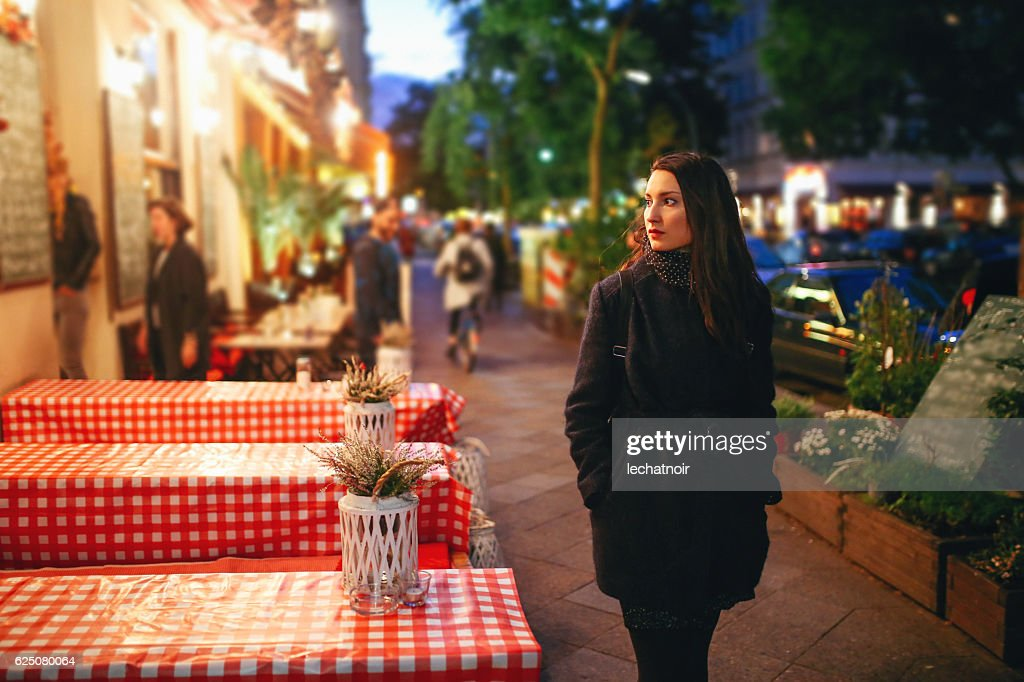 Young woman walking on the streets of Berlin at night : Stock Photo