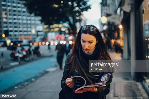 young woman walking on the streets of london - magazine stock pictures, royalty-free photos & images