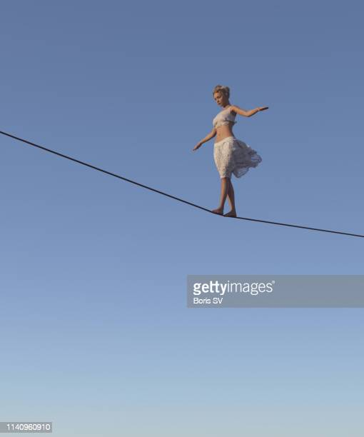 young woman walking on tightrope - balance stock pictures, royalty-free photos & images